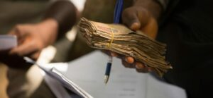 A bundle of money held in a person's hand