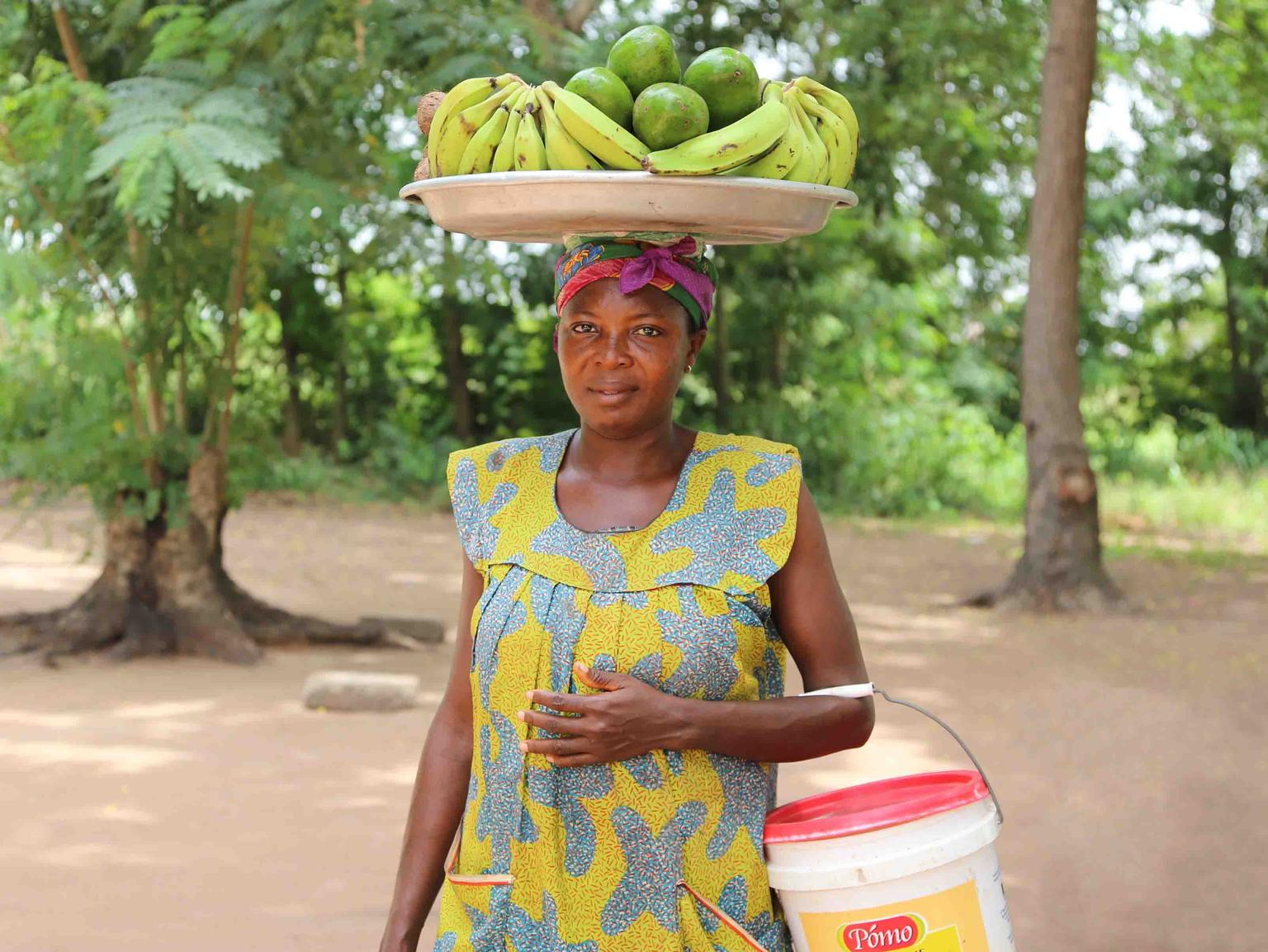 A woman carries fruit in a basket on her head