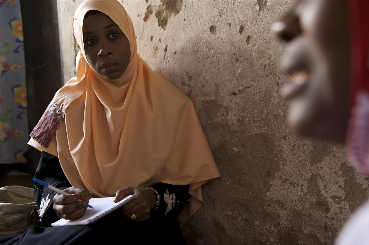 A social worker takes notes while she speaks to a beneficiary